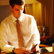 Portrait of a young businessman signing receipt - Stock Photo