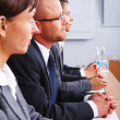 Interested business men and woman sitting in a row - Stock Photo