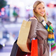 Royalty-Free Stock Photo: Young beautiful woman standing with shopping bags in mall