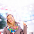 Royalty-Free Stock Photo: Beautiful young lady pointing upwards at copyspace