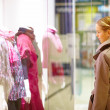 Young woman looking at fashion clothing in shop window - Stock Photo
