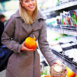 Smiling young woman buying produce in  a supermarket - Lizenzfreies Foto