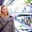Young woman showing a butternut pumpkin in supermarket - Stock Photo