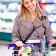 Happy young woman pushing trolley a supermarket - Lizenzfreies Foto