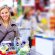 Happy Modern pushing trolley in supermarket - Stock Photo