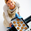 Attractive happy young woman baking cookies - Stock Photo