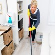 Blond woman in cleaning gear mopping living room floor - 