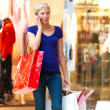Royalty-Free Stock Photo: Busy woman talking on cell while out shopping