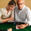 Senior couple playing Blackjack at casino - Stock Photo
