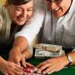 Successfull couple collecting gambling chips at casino - Stock Photo