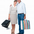 Isolated successful couple carrying shopping - Stock Photo