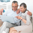 Old couple shopping online with laptop - Stock Photo