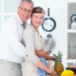Royalty-Free Stock Photo: Senior man  hugging woman in kitchen