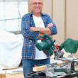 Handy man standing beside electric saw - Stock Photo