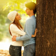 Royalty-Free Stock Photo: Couple standing against a tree and hugging