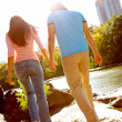 Young couple walking together beside river - Stock Photo