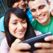 Royalty-Free Stock Photo: Happy young friends looking at modern cellphone