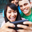 Group of young friends laughing at cellphone - Stock Photo