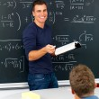 Teacher teaching mathematics in classroom - Stock Photo