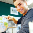 Royalty-Free Stock Photo: Young man pointing at globe in classroom