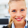 Young business woman with blue eyes smiling happily - Stock Photo