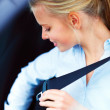 Beautiful young woman putting on her seat belt - Stock Photo