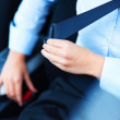 Buckle up - Females hands putting on safety belt - Stock Photo