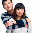 Young man's arms around young asian woman - Stock Photo
