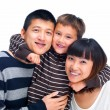 Smiling Asian family smiling together on white - Stock Photo