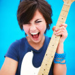 Pretty young woman playing a guitar and singing - Stock Photo
