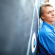 Young guy leaning on graffiti wall - Stock fotografie