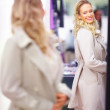 Happy pretty young woman trying out a jacket in a mall - Stock Photo