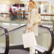 Portrait of a smiling young lady with shopping bag near an escal - Stockfoto