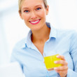 Smiling young business woman holding glass of juice - Zdjęcie stockowe