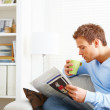 Royalty-Free Stock Photo: Guy sitting on couch with coffee and newspaper