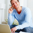 Laughing man using a computer laptop and mobile phone - Stock Photo