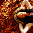 Royalty-Free Stock Photo: Beautiful young girl lying on a bed of dried leaves