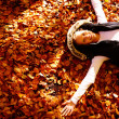Autumn - Woman lying on leaves