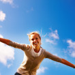 Female spreading her arms under the open blue sky - Stock Photo