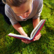 Royalty-Free Stock Photo: Portrait of cute female reading a book on grass