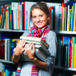 Young smiling lady holding books in library - Stock Photo