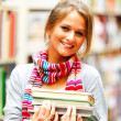 Royalty-Free Stock Photo: Pretty smiling lady holding books in library