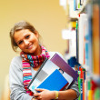 Cute smiling lady holding books in library - Stok fotoğraf