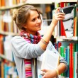 Female university student selecting book from shelf in a library - Stock Photo