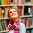 Royalty-Free Stock Photo: Young smiling lady looking upwards in library
