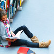 Female student sitting by bookshelf with books in the library - Stock Photo