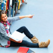 Royalty-Free Stock Photo: Young pretty lady sitting in the library pointing at something