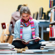 Young lady sitting and reading book in library - Stock Photo