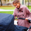 Cute young lady walking with pram - Stock Photo
