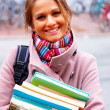 Royalty-Free Stock Photo: Young smiling woman with backpack holding books